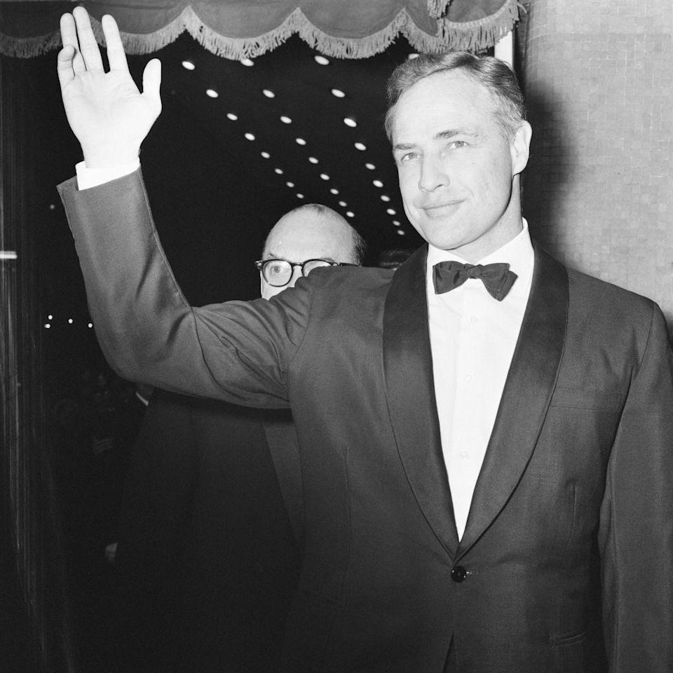<p>Marlon Brando waves to the cameras at the 1967 film premiere of <em>A Countess from Hong Kong</em> in London.</p>