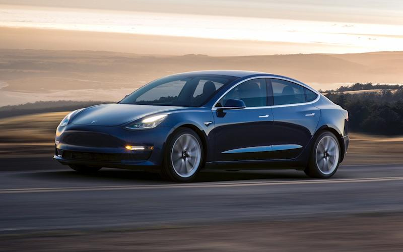 Dark-colored Tesla Model 3 automobile on an empty road with a picturesque landscape behind.
