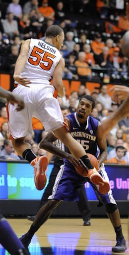 Washington's Scott Suggs (15) looks to pass against Oregon State's Roberto Nelson (55) during the first half of an NCAA college basketball game in Corvallis, Ore., Wednesday Jan. 23, 2013. (AP Photo/Greg Wahl-Stephens)