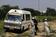 An ambulance leaves after delivering the body of a COVID-19 victim at a graveyard in New Delhi, India, Wednesday, Sept. 16, 2020. India is now second in the world with the number of reported coronavirus infections with over 5.1 million cases, behind only the United States. Its death toll of only 83,000 in a country of 1.3 billion people, however, is raising questions about the way it counts fatalities from COVID-19. (AP Photo/Manish Swarup)
