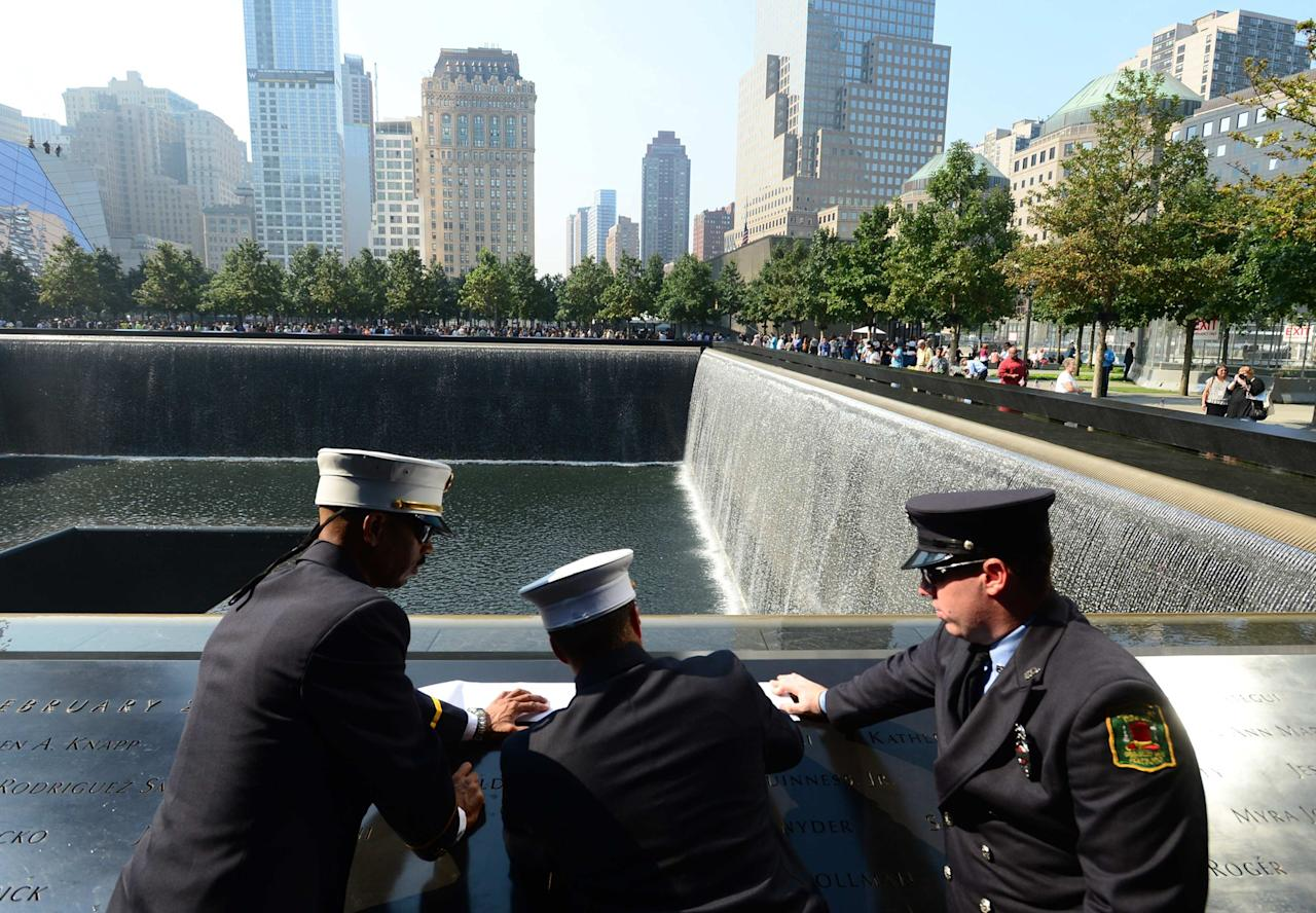 Volunteer firefighters (L to R) Lt. Carlos Santiago, Capt. Alex Avallon and Assistant Engineer Eric Robertson of the Enterprise Hose Company in Hatboro, Pennsylvania stop to remember the victims of Flight 11 at the 9/11 Memorial during a ceremony marking the 12th Anniversary of the attacks on the World Trade Center in New York September 11, 2013. REUTERS/David Handschuh/Pool (UNITED STATES - Tags: DISASTER ANNIVERSARY)