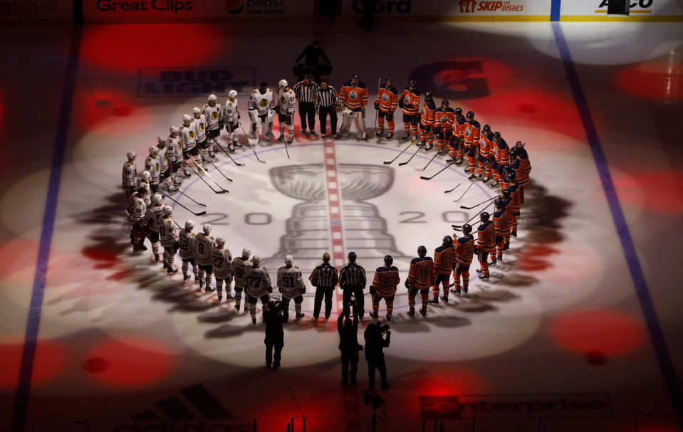 The Edmonton Oilers and the Chicago Blackhawks circle for the national anthem before an NHL hockey Stanley Cup playoff game in Edmonton, Alberta, Saturday, Aug. 1, 2020. (Jason Franson/The Canadian Press via AP)