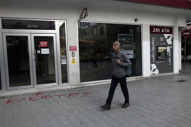 """At the entrance of a closed Laiki Bank graffiti sprayed on the pavement reads in Greek """"thieves"""" as man walks in capital Nicosia, Cyprus, Wednesday, March 20, 2013. Cypriot officials rushed Wednesday to find new ways to stave off financial ruin, including asking Russia for help, after Parliament rejected a plan to contribute to the nation's bailout package by seizing people's bank savings.(AP Photo/Petros Giannakouris)"""