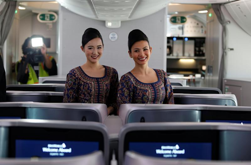 Singapore Airlines stewardesses Karie Choo (L) and Joslyn Hue pose for photos in the business class section of the 787-10 Dreamliner after a delivery ceremony at the Boeing South Carolina plant in North Charleston, South Carolina, U.S., March 26, 2018. Picture taken March 26, 2018. REUTERS/Randall Hill