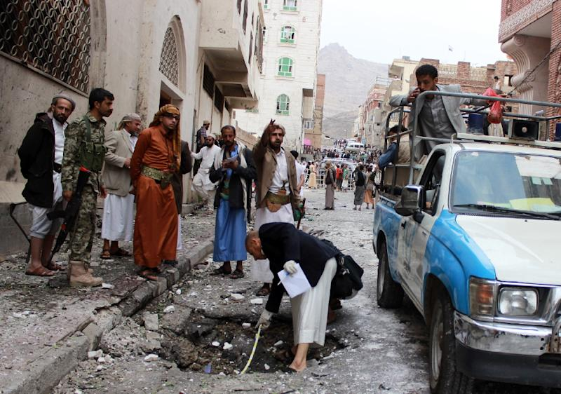 Yemeni civilians, security forces and forensics inspect the site of a car bomb explosion near a mosque on July 29, 2015 in the capital Sanaa