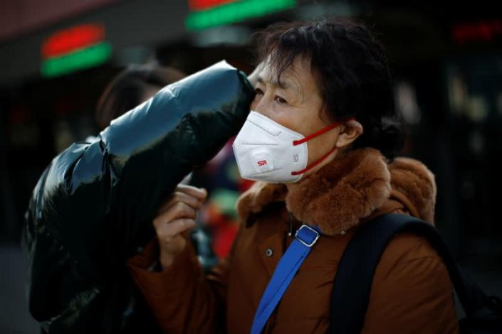 A woman gets help to fit her face mask outside Beijing Railway Station as the country is hit by an outbreak of the new coronavirus, in Beijing