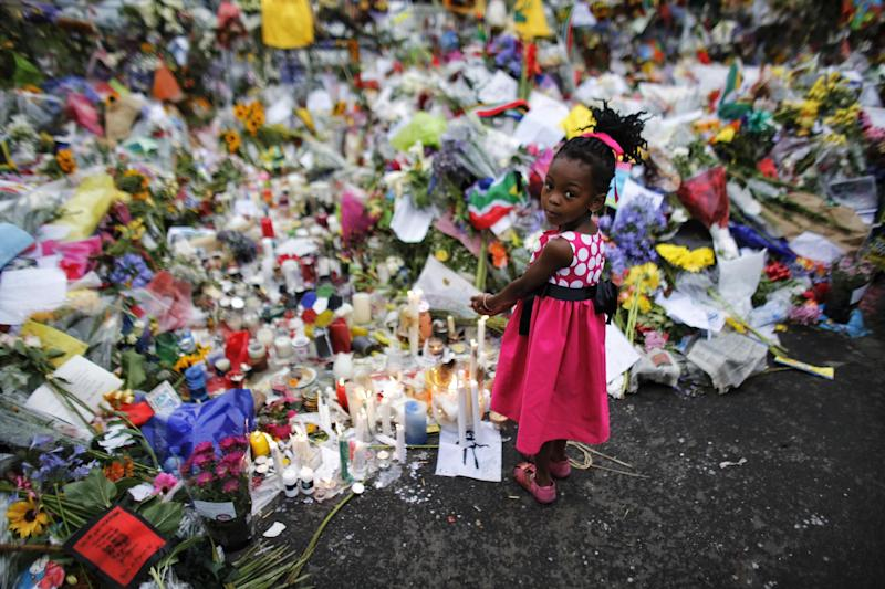 Four years old Bokamoso warms her hands over candles placed between flowers outside of the house of former South African President Nelson Mandela in Johannesburg, Monday, Dec. 9, 2013. Scores of heads of state and government and other foreign dignitaries, including royalty, are beginning to converge on South Africa as the final preparations for Tuesday's national memorial service for liberation struggle icon Nelson Mandela are put in place. (AP Photo/Markus Schreiber)