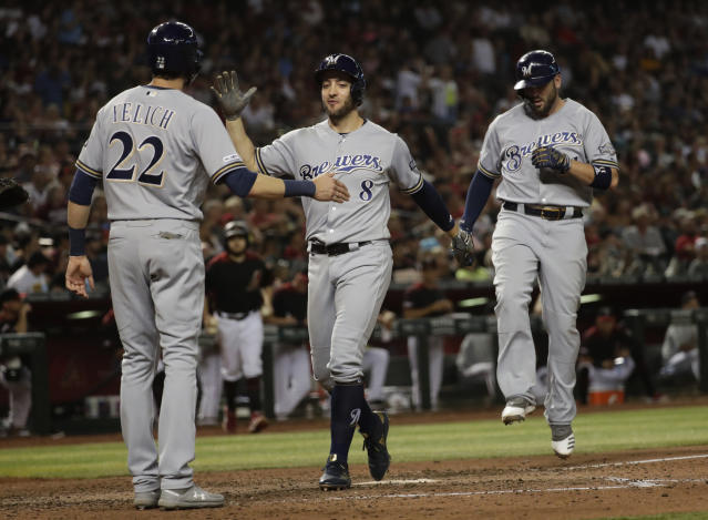 Milwaukee Brewers' Ryan Braun (8) celebrates with Christian Yelich (22) and Mike Moustakas after Moustakas hit a three-run home run against the Arizona Diamondbacks during the eighth inning of a baseball game, Saturday, July 20, 2019, in Phoenix. (AP Photo/Matt York)
