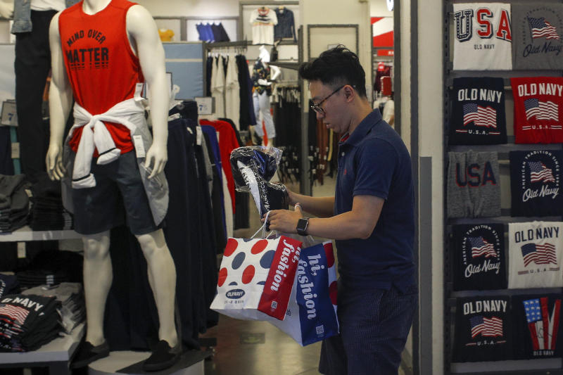 A man buys clothes from an American clothing store having a promotion sale at a shopping mall in Beijing, Monday, July 15, 2019. China's economic growth sank to its lowest level in at least 26 years in the quarter ending in June, adding to pressure on Chinese leaders as they fight a tariff war with Washington. (AP Photo/Andy Wong)