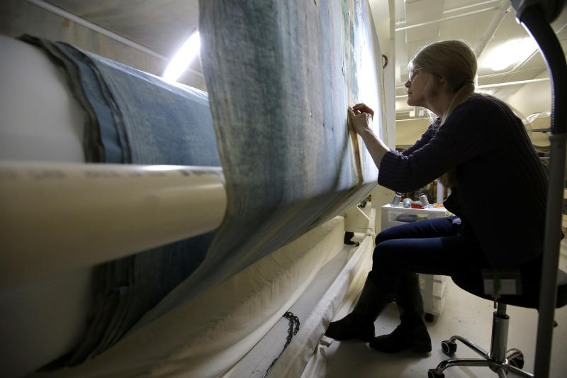 """In this Tuesday, Nov. 7, 2017 photo textile conservator Kate Tarleton, of Rochester, Mass., works to restore a portion of the 1848, """"Grand Panorama of a Whaling Voyage Round the World,"""" at the New Bedford Whaling Museum, in New Bedford, Mass. The artifact is believed to be the longest painting in the world at about a quarter mile long. (AP Photo/Steven Senne)"""
