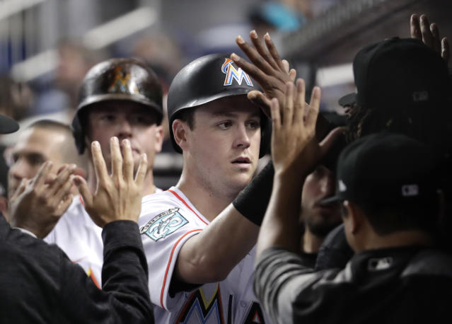Miami Marlins' Brian Anderson is congratulated in the dugout after scoring on a double by JT Riddle during the third inning of a baseball game against the San Francisco Giants, Tuesday, June 12, 2018, in Miami. (AP Photo/Lynne Sladky)