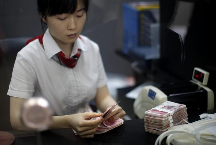 Employee of the Industrial and Commercial Bank of China Ltd counts money at one of bank's branches at the Shanghai Free Trade Zone in Pudong district