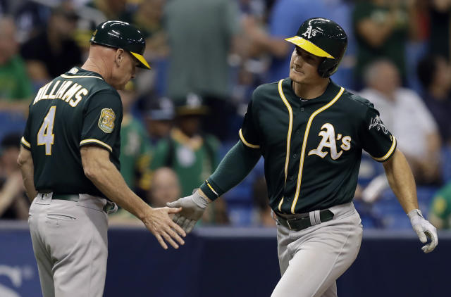 Oakland Athletics' Matt Chapman, right, shakes hands with third base coach Matt Williams after Chapman hit a home run off Tampa Bay Rays pitcher Sergio Romo during the ninth inning of a baseball game, Saturday, Sept. 15, 2018, in St. Petersburg, Fla. (AP Photo/Chris O'Meara)