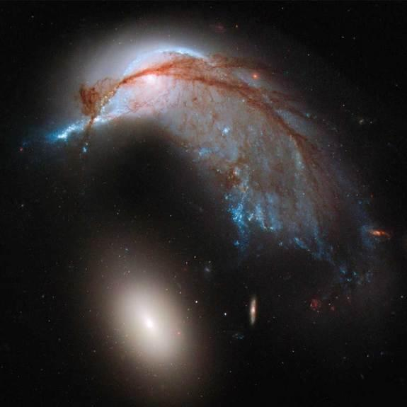 This image shows the two galaxies interacting. NGC 2936, once a standard spiral galaxy, and NGC 2937, a smaller elliptical, bear a striking resemblance to a penguin guarding its egg. Image released June 20, 2013.