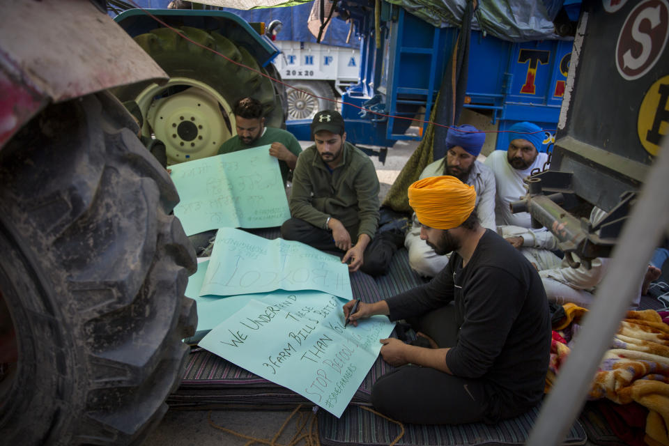 "Young farmers make placards as they block a major highway during a protest against new farming laws they say will result in exploitation by corporations, eventually rendering them landless, at the Delhi-Haryana state border, India, Tuesday, Dec. 1, 2020. The busy, nonstop, arterial highways that connect most northern Indian towns to this city of 29 million people, now beat to the rhythm of never-heard-before cries of ""Inquilab Zindabad"" (""Long live the revolution""). Tens and thousands of farmers, with colorful distinctive turbans and long, flowing beards, have descended upon its borders where they commandeer wide swathes of roads. (AP Photo/Altaf Qadri)"