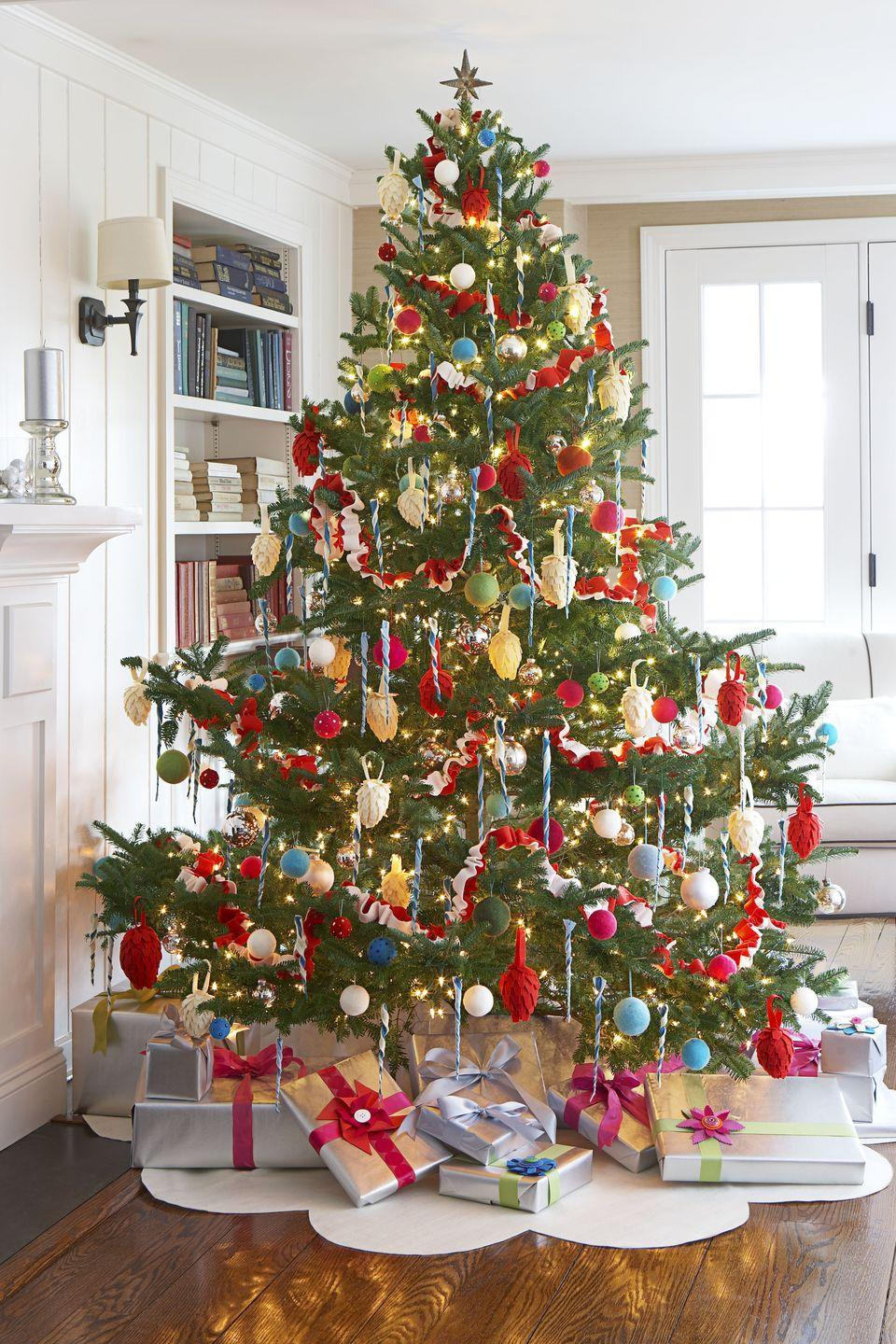 """<p><span class=""""redactor-invisible-space"""">Put your love of maximalist decor on full display with a tree that's decked out in colorful ornaments, blue ribbons, and loads of warm lights. </span> </p>"""
