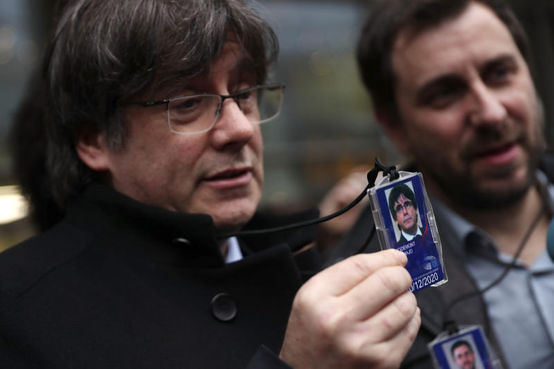 Catalonia's former regional president Carles Puigdemont, left, shows his accreditation badge as he stands next to former Catalan regional minister Antoni Comin outside the European Parliament in Brussels, Friday, Dec. 20, 2019. In a potentially stinging reversal for Spanish justice authorities, the European Union's top court ruled that a former Catalan official serving a prison sentence for his role in a banned independence referendum two years ago had the right to parliamentary immunity when he was on trial. (AP Photo/Francisco Seco)