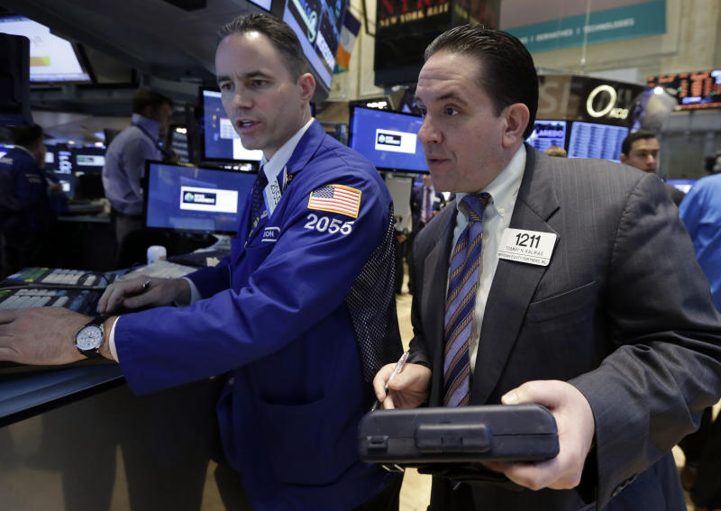 Specialist Jason Hardzewicz works with trader Tommy Kalikas on the floor of the New York Stock Exchange, Tuesday, April 22, 2014. Stock futures edged higher as more companies reported first quarter earnings. (AP Photo/Richard Drew)