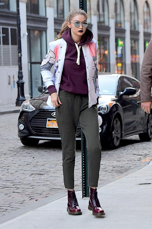 <p>In a dark purple hooded sweatshirt with a Rochambeau printed bomber, grey sweatpants, Dr. Martens boots and silver rounded aviator sunglasses while out in New York City. </p>