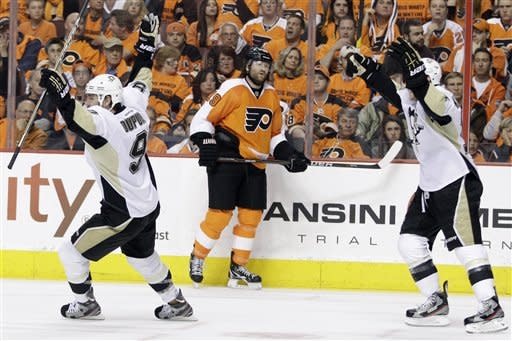 Pittsburgh Penguins' Pascal Dupuis, left, and Chris Kunitz, right, celebrate after Dupuis' goal as Philadelphia Flyers' Scott Hartnell looks on in the second period of Game 4 in a first-round NHL Stanley Cup playoffs hockey series on Wednesday, April 18, 2012, in Philadelphia. (AP Photo/Matt Slocum)