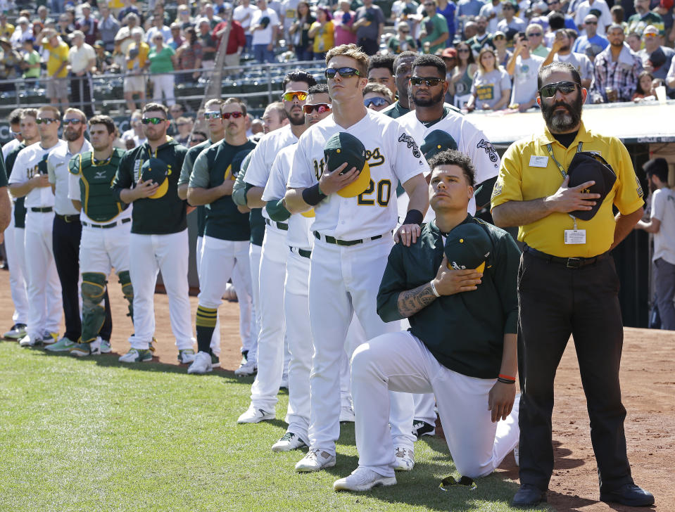 Oakland Athletics' Mark Canha (20) places his hand on the shoulder of Bruce Maxwell as Maxwell takes a knee during the national anthem prior to a baseball game against the Texas Rangers, Sunday, Sept. 24, 2017, in Oakland, Calif. (AP)
