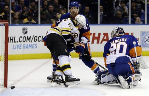 Boston Bruins left wing Brad Marchand (63) blocks New York Islanders defenseman Andrew MacDonald (47) as a goal by Bruins Adam McQuaid goes in during the first period of their NHL hockey game at Nassau Coliseum in Uniondale, N.Y., Tuesday, Feb. 26, 2013. Islanders goalie Evgeni Nabokov (20) watches the puck. (AP Photo/Kathy Willens)
