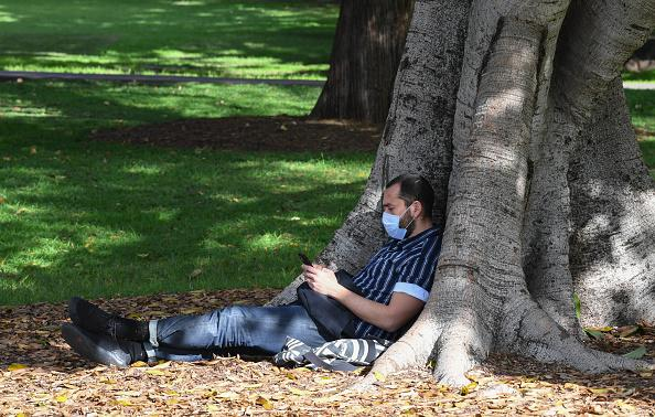 A man wearing a face mask reads his mobile phone as people gather in the Domain in Sydney, Australia.