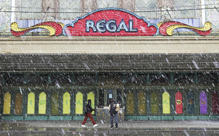 A woman walks past a man standing under the marquee of the Avalon Regal Theater as snow falls in the 1600 block of East 79th Street Saturday, April 27, 2019, in Chicago. (John J. Kim/Chicago Tribune via AP)