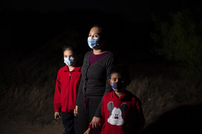 FILE - In this March 24, 2021, file photo, Fatima Nayeli, 13, center, talks to journalists as she holds the hand of her sister, Cynthia Stacy, 8, and Davidson Jair, 7, after they were smuggled on an inflatable raft across the Rio Grande river in Roma, Texas. All three children traveled from El Salvador in the hope of reaching relatives living in the U.S. Confronted with a stream of unaccompanied children crossing the border from Mexico, the U.S. government has awarded shelter-construction and management contracts to private companies that critics say may not be equipped to adequately care for the minors. (AP Photo/Dario Lopez-Mills, File)