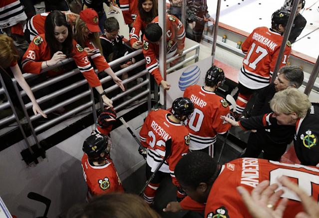Chicago Blackhawks fans greet with players before they get on the ice before Game 2 of the Western Conference finals in the NHL hockey Stanley Cup playoffs against the Los Angeles Kings in Chicago on Wednesday, May 21, 2014. (AP Photo/Nam Y. Huh)