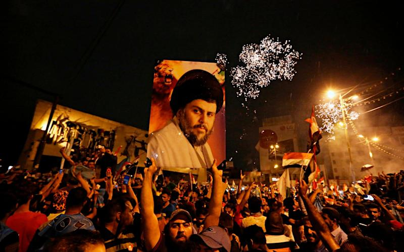 Followers of Shia cleric Moqtada al-Sadr, seen in the poster, celebrate in Tahrir Square, Baghdad, Iraq, early Monday - AP