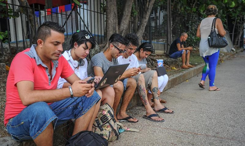 Cubans use their mobile devices to connect to the Internet via wifi in a street of Havana, on July 2, 2015 (AFP Photo/Yamil Lage)