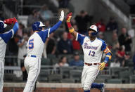 Atlanta Braves' Ronald Acuna Jr., right, high-five Freddie Freeman after hitting a home run during the third inning of the team's baseball game against the Miami Marlins on Wednesday, April 14, 2021, in Atlanta. (AP Photo/Brynn Anderson)