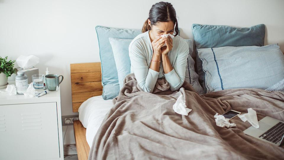Woman with flu in bed, she use home medicine to handle sickness.