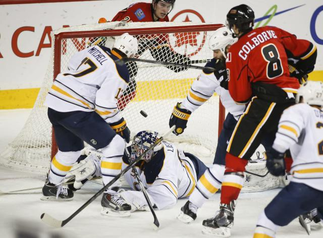 Buffalo Sabres goalie Nathan Lieuwen, centre, scrambles on the ice as Calgary Flames' Joe Colborne scores during second period NHL hockey action in Calgary, , Alberta, on Tuesday March 18, 2014. (AP Photo/The Canadian Press, Jeff McIntosh)