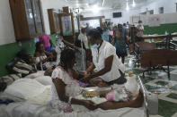 """Nurse Gabrielle Lagrenade treats a patient at the Immaculate Conception Hospital, also known as the General Hospital of Les Cayes, Haiti, Sunday, Aug. 22, 2021, a week after a 7.2 magnitude earthquake. Lagrenade and her 21-year-old daughter Bethsabelle have been sleeping outside since Aug. 14, and describes her current living conditions simply as """"inappropriate,"""" but she continues arriving for her daily shift at the hospital. (AP Photo/Matias Delacroix)"""