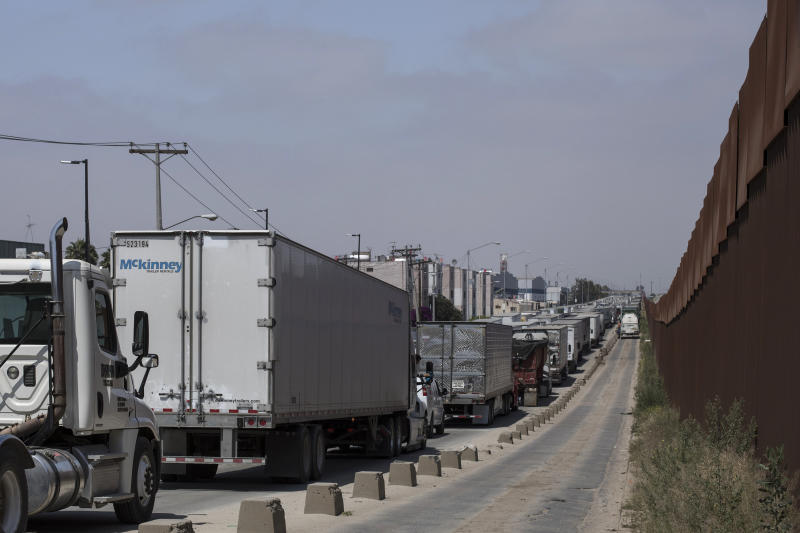 Trucks line up to cross into the United States at the border in Tijuana, Mexico, Friday, June 7, 2019. Companies have been rushing to ship as many goods as possible out of Mexico to get ahead of possible tariffs threatened by President Donald Trump, hurriedly sending cars, appliances and construction materials across the border to beat Monday's deadline. (AP Photo/Hans-Maximo Musielik)