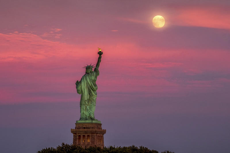 The full moon rises behind the Statue of Liberty at sunset in New York City, Monday, July 15, 2019, on the night before the 50th anniversary of the Apollo 11 moon launch. (AP Photo/J. David Ake)