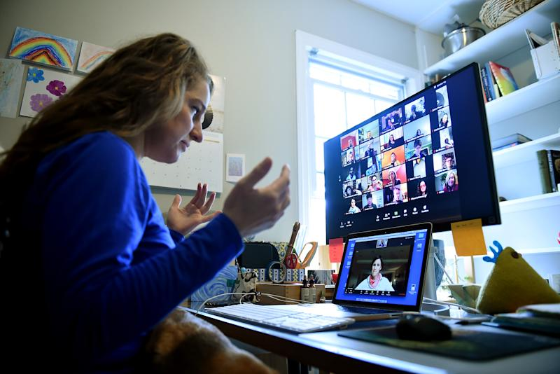 Lauryn Morley, a lower school substitute teacher for the Washington Waldorf School in Bethesda, Maryland, talks to Clare Andre (laptop), a 7th grade teacher and co-chair of the lower school, from her home due to the Coronavirus outbreak on April 1, 2020 in Arlington, Virginia. - Her role in the school changed significantly when Coronavirus hit. She was previously working part time to support teachers when they needed to be absent from the classroom and now she helps them to build skills with new digital platforms so they can continue to teach in the best way for their students and their families.The middle school (grades 6-8) has most regularly been using Zoom and the lower grades have been using Zoom with parents. (Photo by Olivier DOULIERY / AFP) (Photo by OLIVIER DOULIERY/AFP via Getty Images)