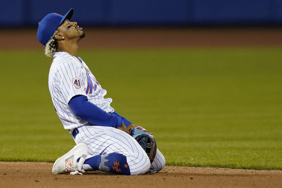 New York Mets shortstop Francisco Lindor reacts after a failed double-play attempt on a ball hit by Arizona Diamondbacks' Zac Gallen during the third inning of a baseball game, Friday, May 7, 2021, in New York. A runner was forced at second, and a run scored. (AP Photo/John Minchillo)