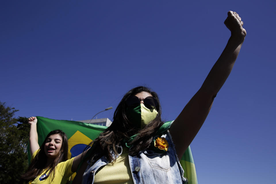 Supporters of Brazil's President Jair Bolsonaro shout slogans during a protest against former Minister of Justice Sergio Moro and the Supreme Court, in front of the Planalto presidential palace, in Brasilia, Brazil, Sunday, May 3, 2020. (AP Photo/Eraldo Peres)