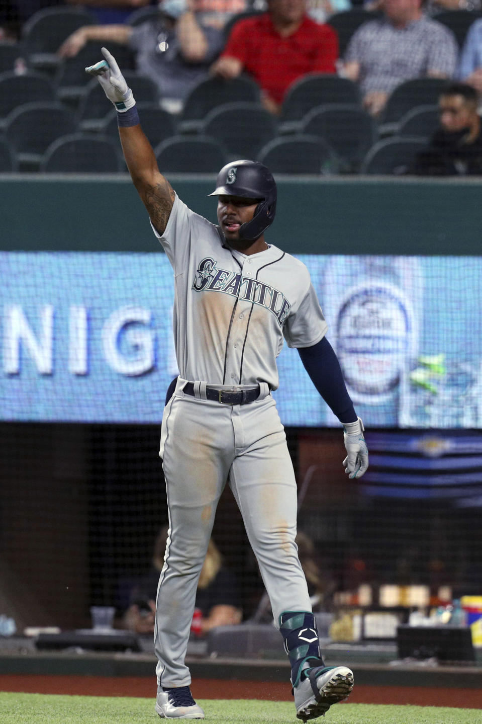 Seattle Mariners' Taylor Trammell gestures toward Mitch Haniger after scoring against the Texas Rangers during the seventh inning of a baseball game Friday, May 7, 2021, in Arlington, Texas. (AP Photo/Richard W. Rodriguez)