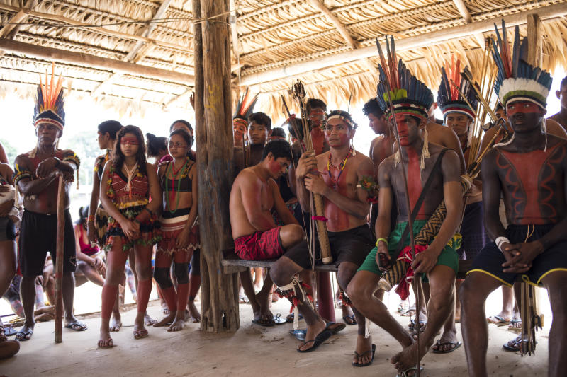In this Sept. 3, 2019 photo, indigenous villagers listen to speakers during a meeting of Tembé tribes at the Tekohaw indigenous reserve, Para state, Brazil. Some of the men wore a type of red face paint that signified they were ready for war. Recent clashes saw the Tembe burning the trucks and equipment of illegal loggers on their territory, which is located in a Brazilian state plagued by thousands of fires burning on cleared jungle lands. (AP Photo/Rodrigo Abd)