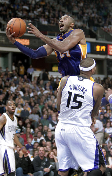Los Angeles Lakers guard Kobe Bryant is fouled by Sacramento Kings center DeMarcus Cousins as he drives to the basket during the second half of an NBA basketball game in Sacramento, Calif., Wednesday, Nov. 21, 2012. The Kings won 113-97. (AP Photo/Rich Pedroncelli)
