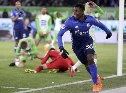 Schalke's Breel Embolo, right, celebrates an own goal scored by Wolfsburg's Robin Knoche, rear left, during the German Bundesliga soccer match between VfL Wolfsburg and FC Schalke 04 in Wolfsburg, Germany, Saturday, March 17, 2018. (AP Photo/Michael Sohn)