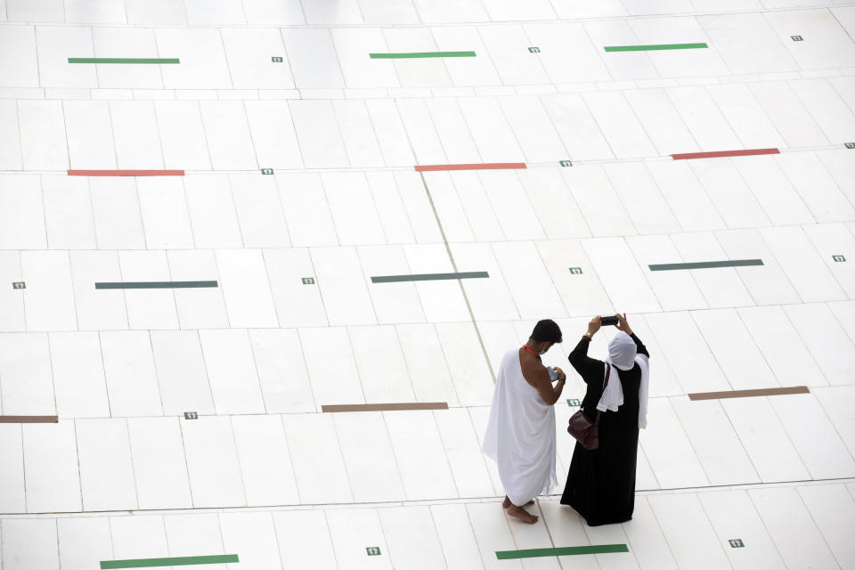 A Muslim pilgrim couple takes mobile shots at the Grand Mosque, as they stand on social distancing signs, a day before the annual hajj pilgrimage, Saturday, July 17, 2021. The pilgrimage to Mecca required once in a lifetime of every Muslim who can afford it and is physically able to make it, used to draw more than 2 million people. But for a second straight year it has been curtailed due to the coronavirus with only vaccinated people in Saudi Arabia able to participate. (AP Photo/Amr Nabil)