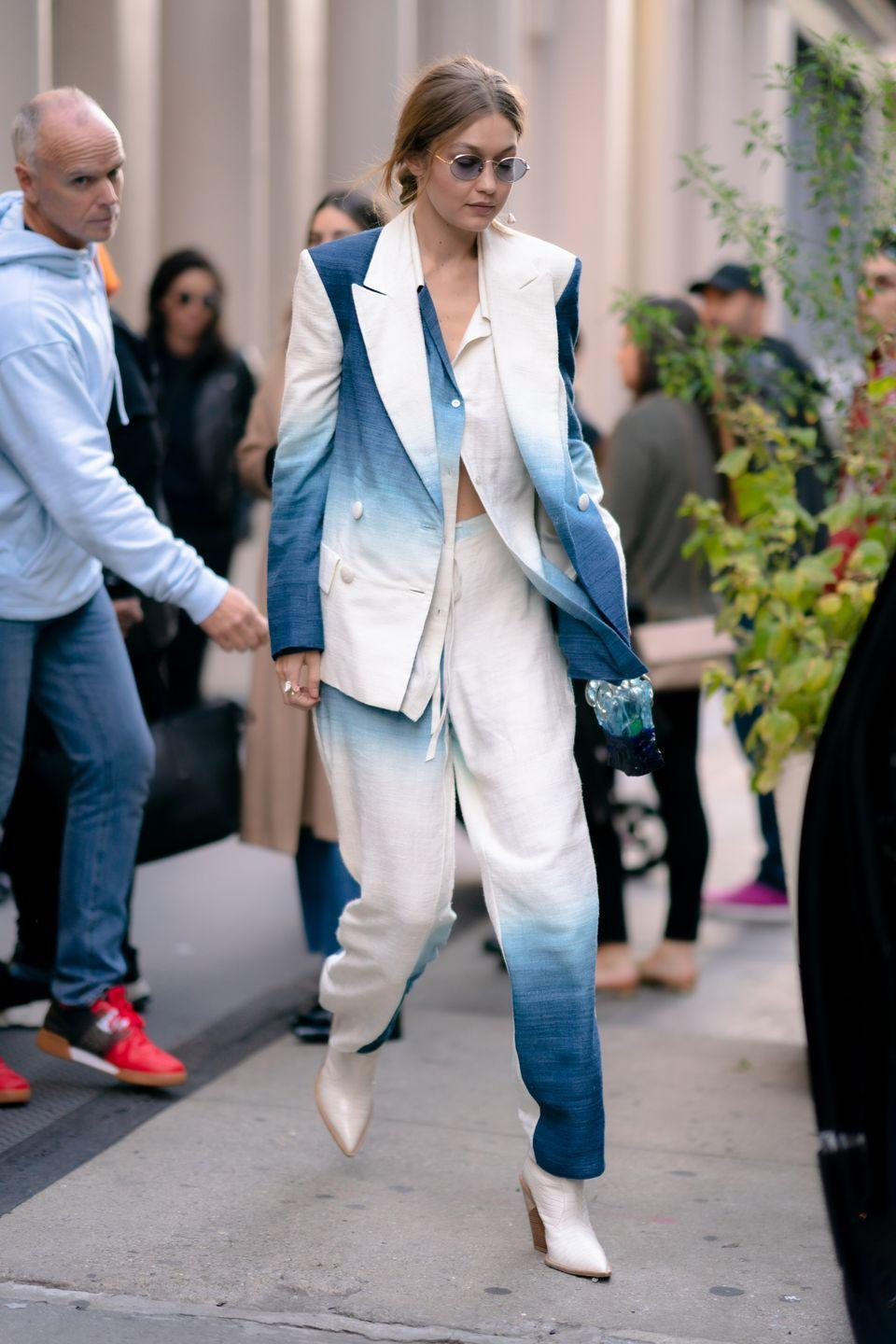 <p>In a blue and white suit by Oscar de la Renta, blue circle shades, and white heeled boots.</p>
