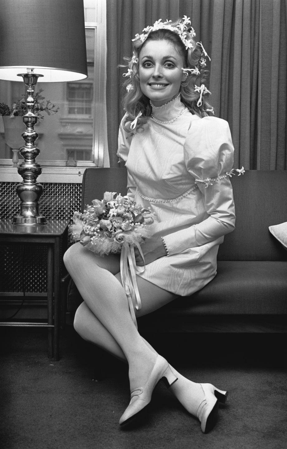 """<p>Tate's wedding look—a long sleeve mini dress and flowers scattered in her hair—instantly became iconic. The dress sold <a href=""""https://www.cnn.com/style/article/sharon-tate-wedding-dress-scli-intl/index.html"""" rel=""""nofollow noopener"""" target=""""_blank"""" data-ylk=""""slk:at an auction last year"""" class=""""link rapid-noclick-resp"""">at an auction last year</a> for $56,000 to an anonymous buyer. </p>"""