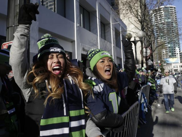 Western Washington University students Teena Thach (L), 21, and Shawna Mori, 20, stand along 4th Avenue at the Super Bowl victory parade for the Seattle Seahawks in downtown in Seattle, Washington February 5, 2014. Up to 500,000 Seattle Seahawks fans were expected to brave sub-freezing temperatures to celebrate the football team's first Super Bowl title at a parade set to wind through the city's downtown on Wednesday. REUTERS/Jason Redmond (UNITED STATES - Tags: SPORT FOOTBALL EDUCATION)