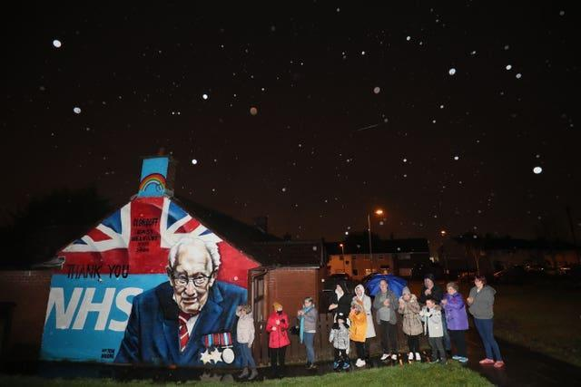 Local residents stand beside a mural of Captain Sir Tom Moore in Clonduff, east Belfast, as they join in with a nationwide clap